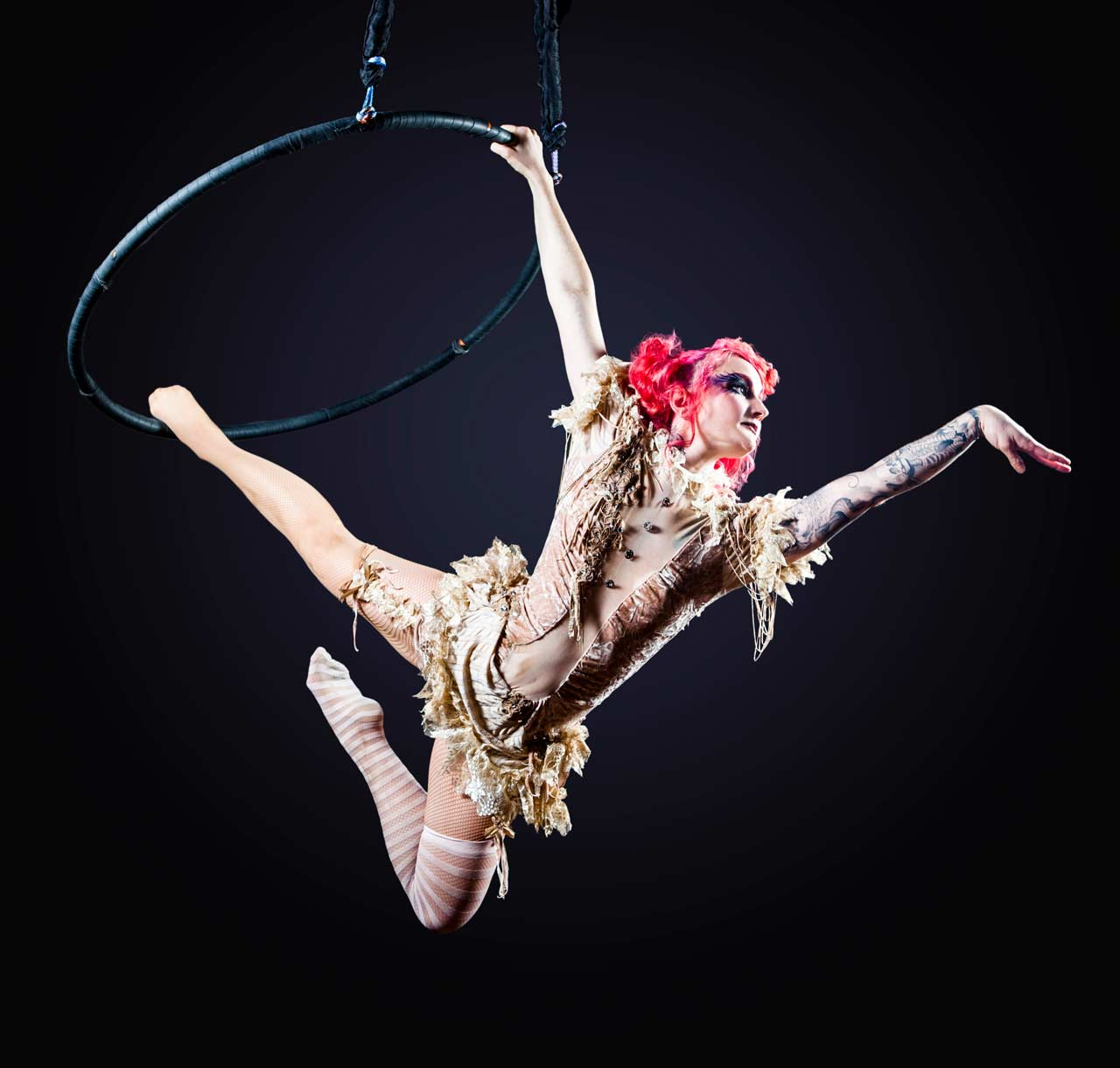 Photo of a solo aerialist using a trapeze.